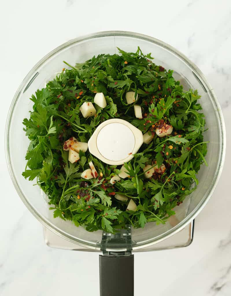 Top view of a food processor full of parsley, garlic and chili flakes.