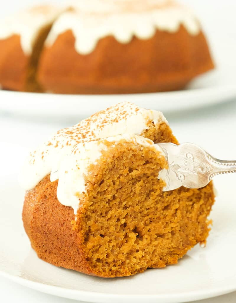 Close up of a slice of pumpkin bundt cake with cream cheese topping. A whole cake in the background.