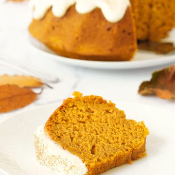 A slice of pumpkin bundt cake with cream cheese frosting on a white plate.
