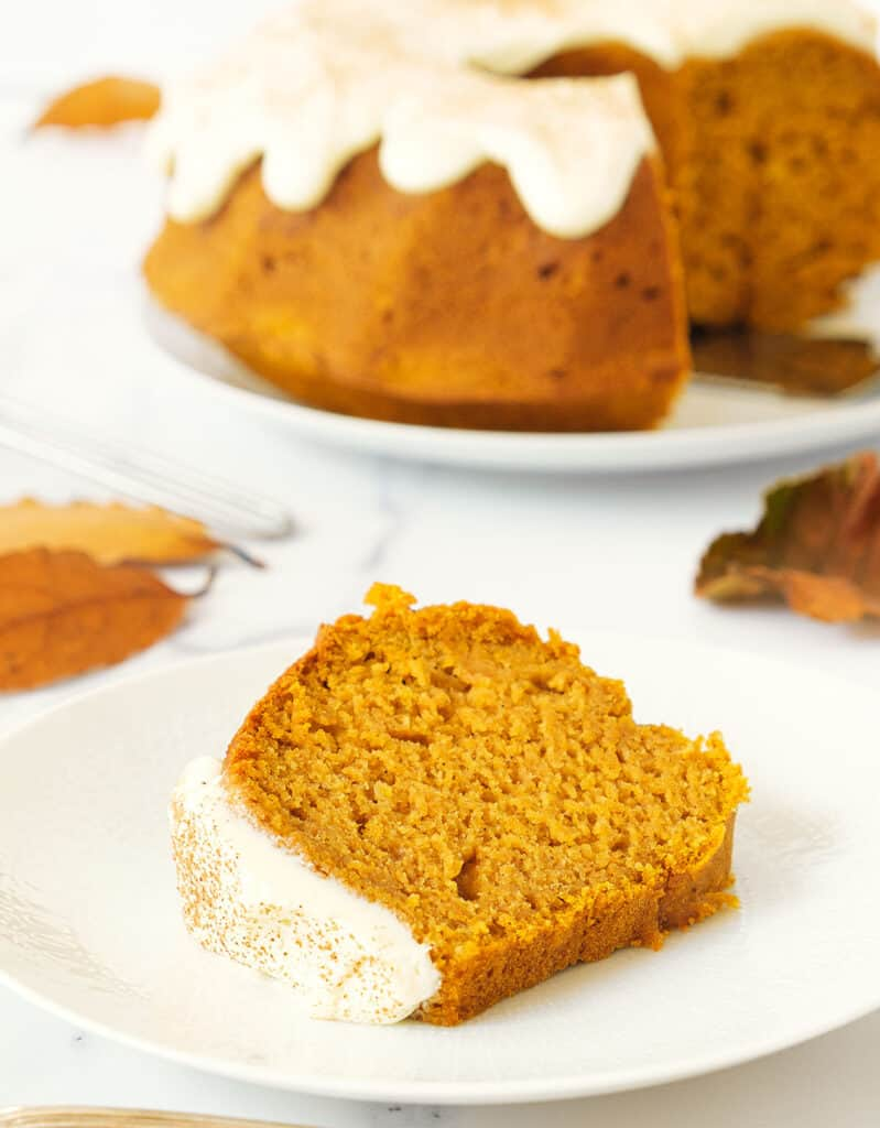 A slice of pumpkin bundt cake on a white plate, orange leaves and whole cake in the background.