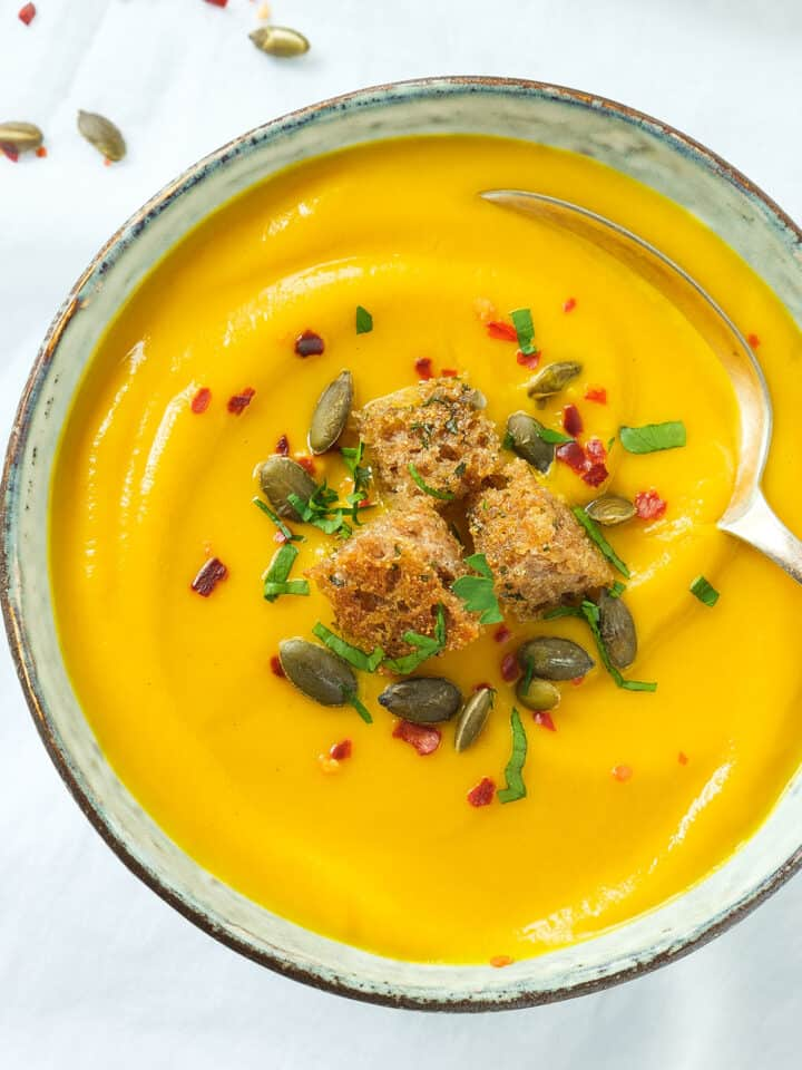 Top view of a bowl of pumpkin carrot soup garnished with croutons, pumpkin seeds and chili flakes.