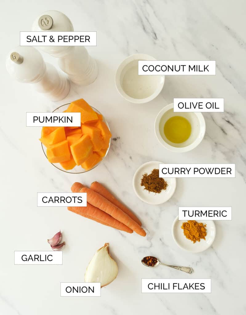 The ingredients for the pumpkin carrot soup are arranged over a white countertop.