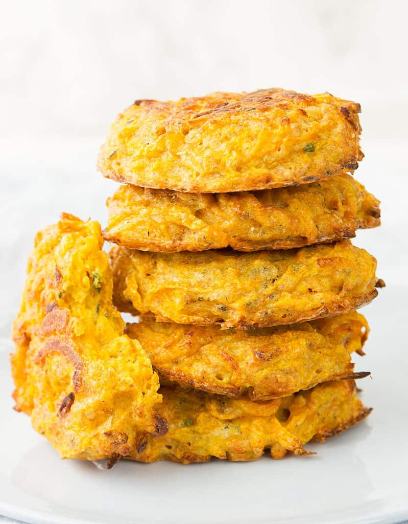 Close-up of a pile of crispy butternut squash fritters over a white background.