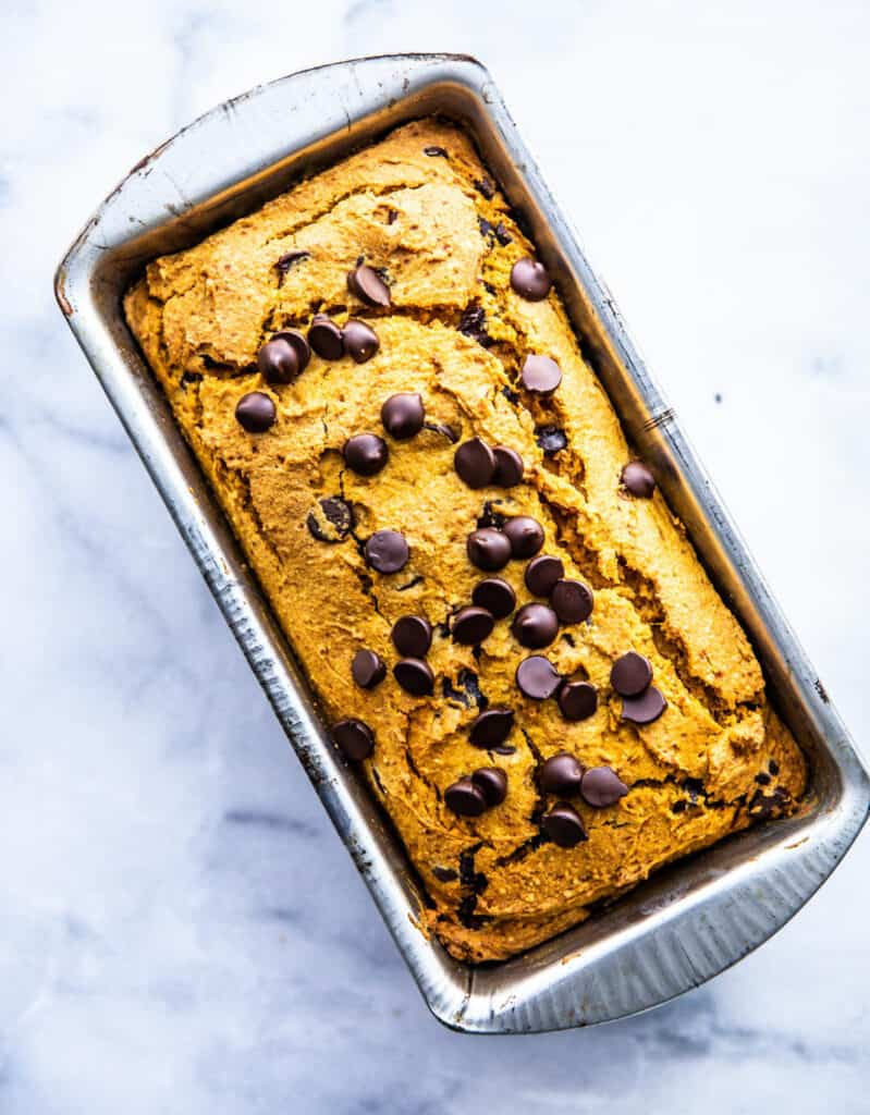 Vegan pumpkin bread with chocolate chips in a loaf pan over a white background by Cotter Crunch.