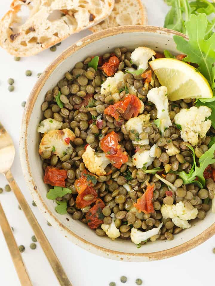 Top view of a bowl full of green lentil salad.
