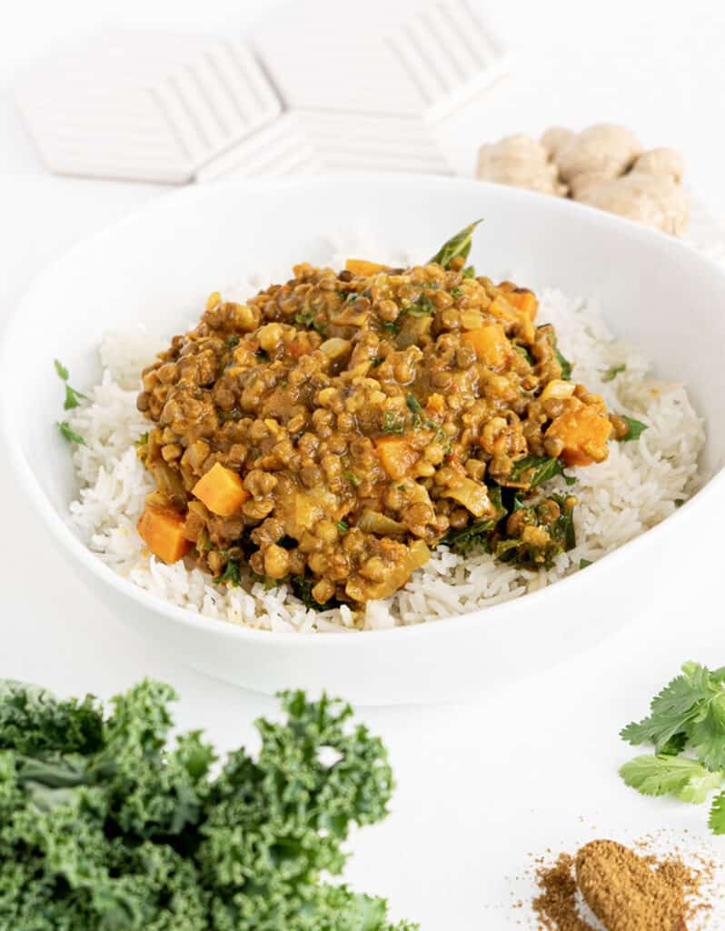 A white bowl full of rice and green lentil curry over a white background.