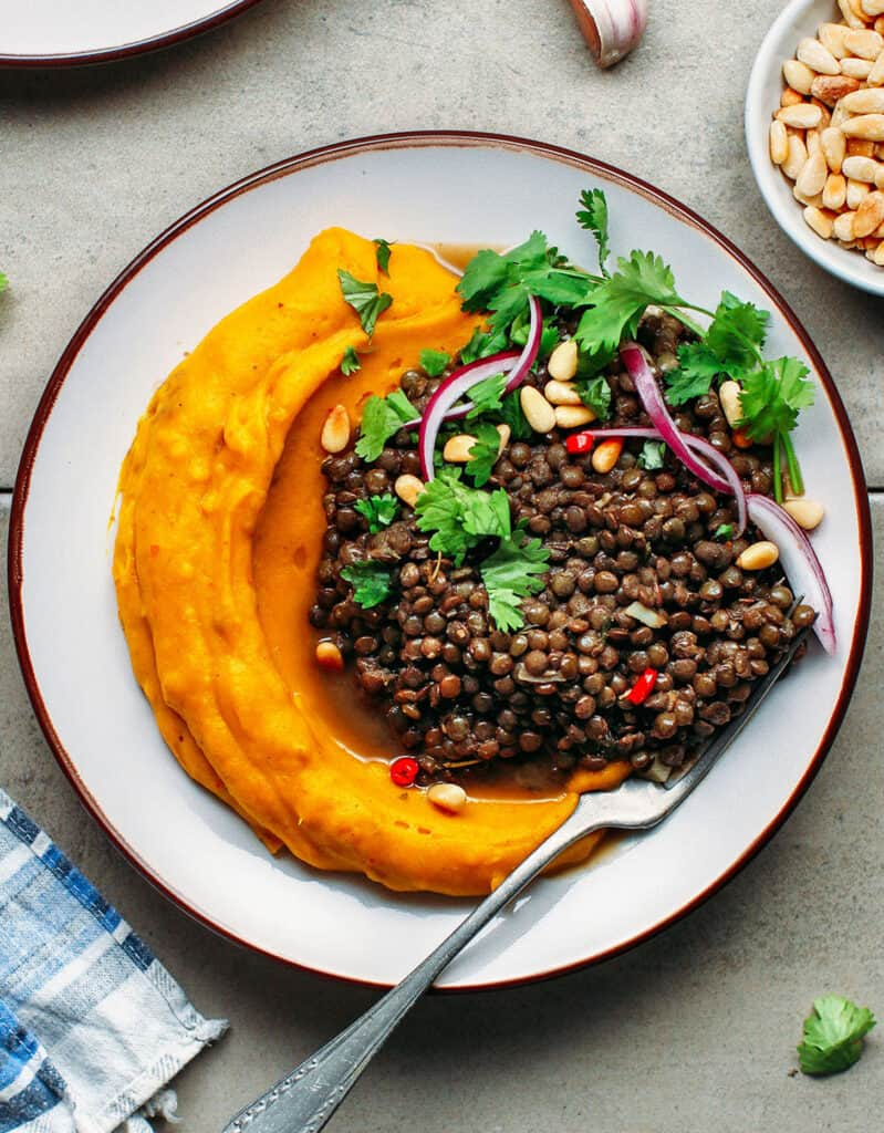 Top view of another green lentil recipe with a plate full of mashed pumpkin and lentils over a grey background.