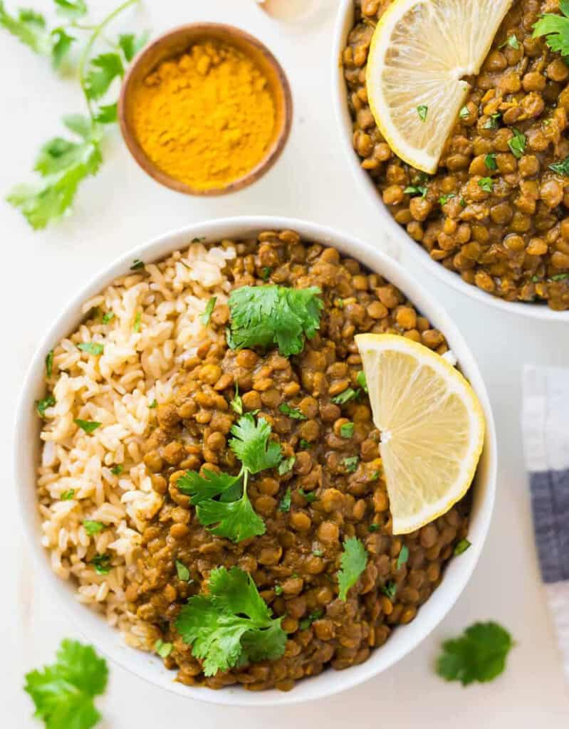 Top view of two white bowls full of rice, lentil curry, coriander leaves and a lemon wedge.
