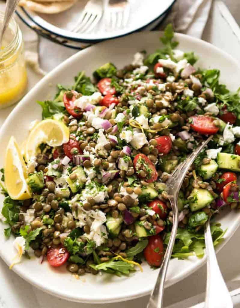 A white serving plate with green lentil salad, cherry tomatoes, crumbled feta and lemon wedges.