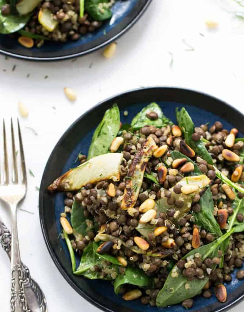 Top view of two blue plates full of green lentils salad, spinach and toasted pinenuts over a white background.