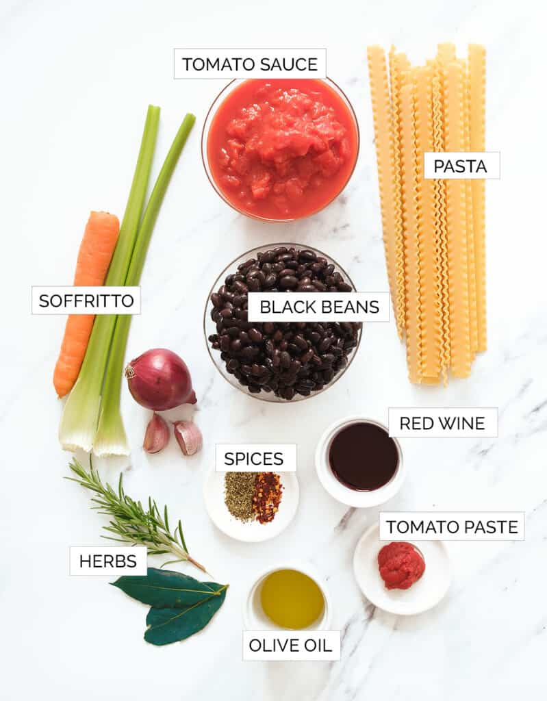 The ingredients for this pasta with black bean recipe are arranged over a white background.