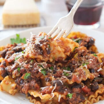 Close-up of a white plate full of pasta with black bean ragu'.