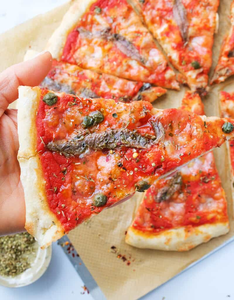 Close-up of a slice of anchovy pizza topped with anchovies, capers and oregano.