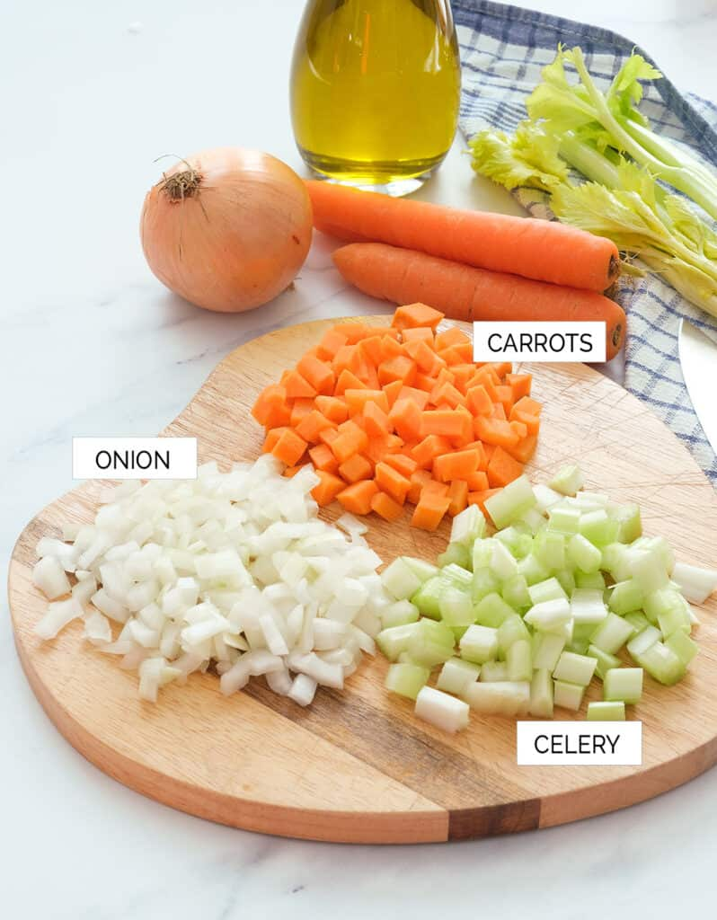 Close-up of a chopping board with the ingredients to make the Italian soffritto: onion, carrots, celery and olive oil.