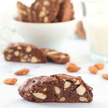 Close-up of vegan biscotti with almonds over a white background.