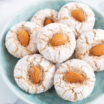 Close-up of a turquoise bowl with white almond cookies.