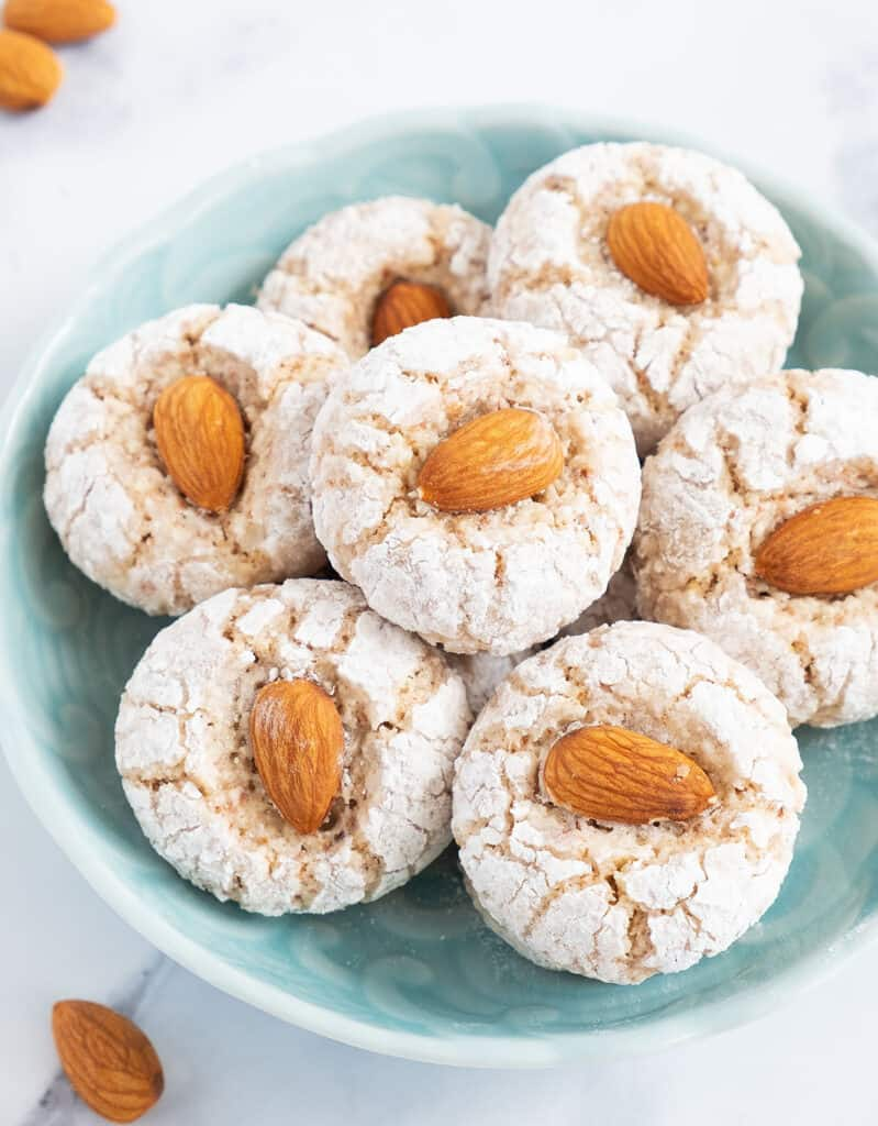 White almond cookies topped with almonds on a turquoise bowl.