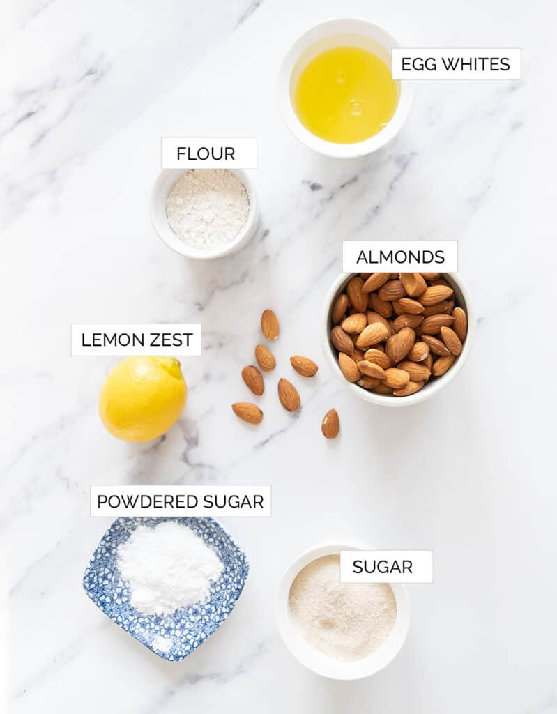 The ingredients to make these easy almond cookies are arranged over a white background.