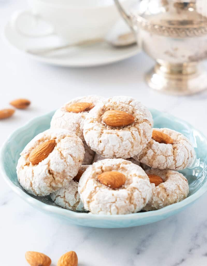 A turquoise bowl with almond cookies, and a white cup and a silver sugar bowl in the background.