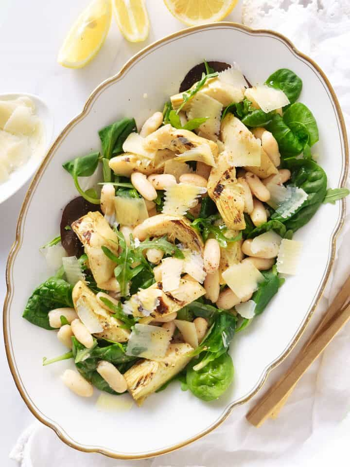 Top view of a white serving plate full of artichoke salad with greens, beans and shaved parmesan.