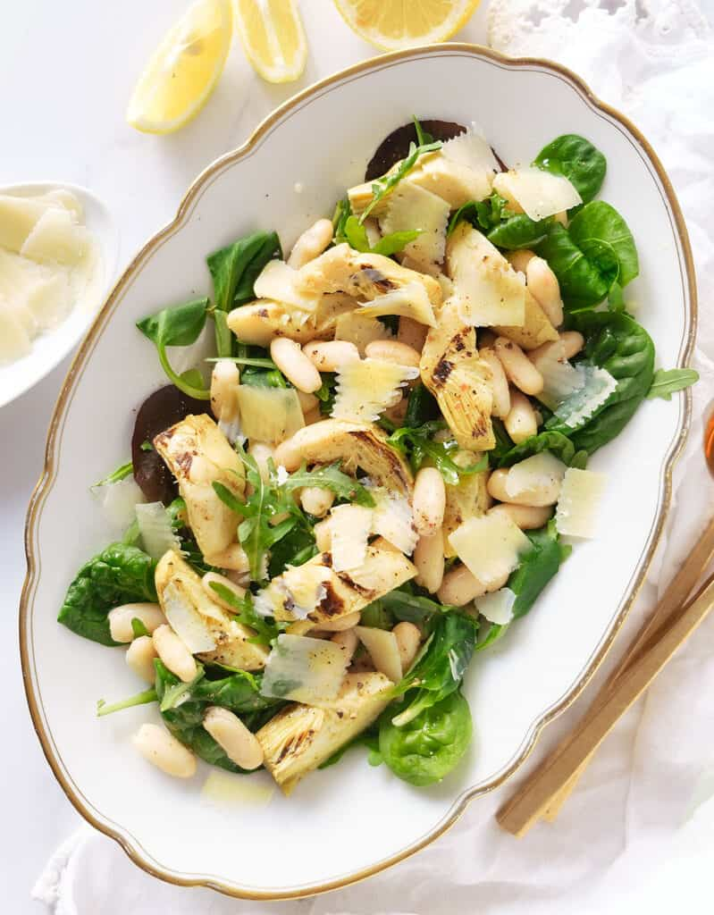 Top view of a white serving plate full of artichoke salad garnished with shaved parmesan.