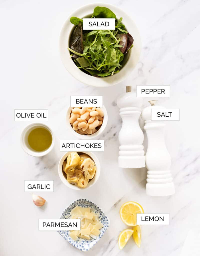 The ingredients for this easy artichoke salad are arranged over a white background.