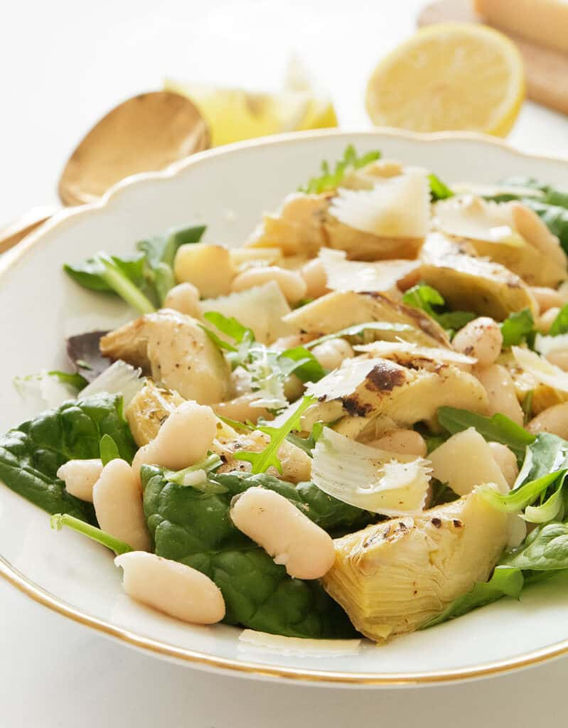 Close-up of the artichoke salad with beans and green leaves, lemon wedges in the background.