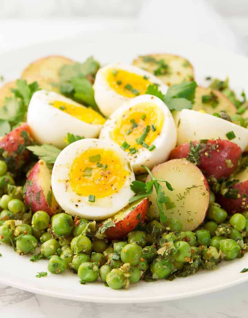 Peas, potato and egg salad on a white plate, a quick pea recipe perfect in spring time.