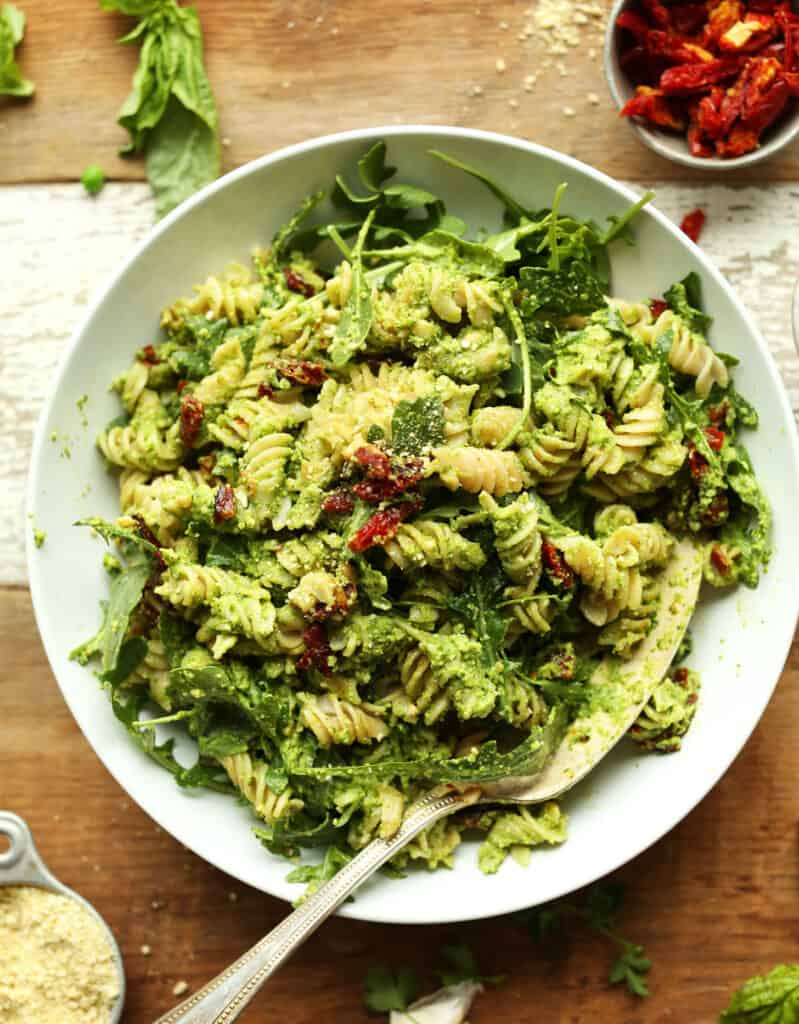 Top view of a white bowl with green pea pesto pasta with sun dried tomatoes.