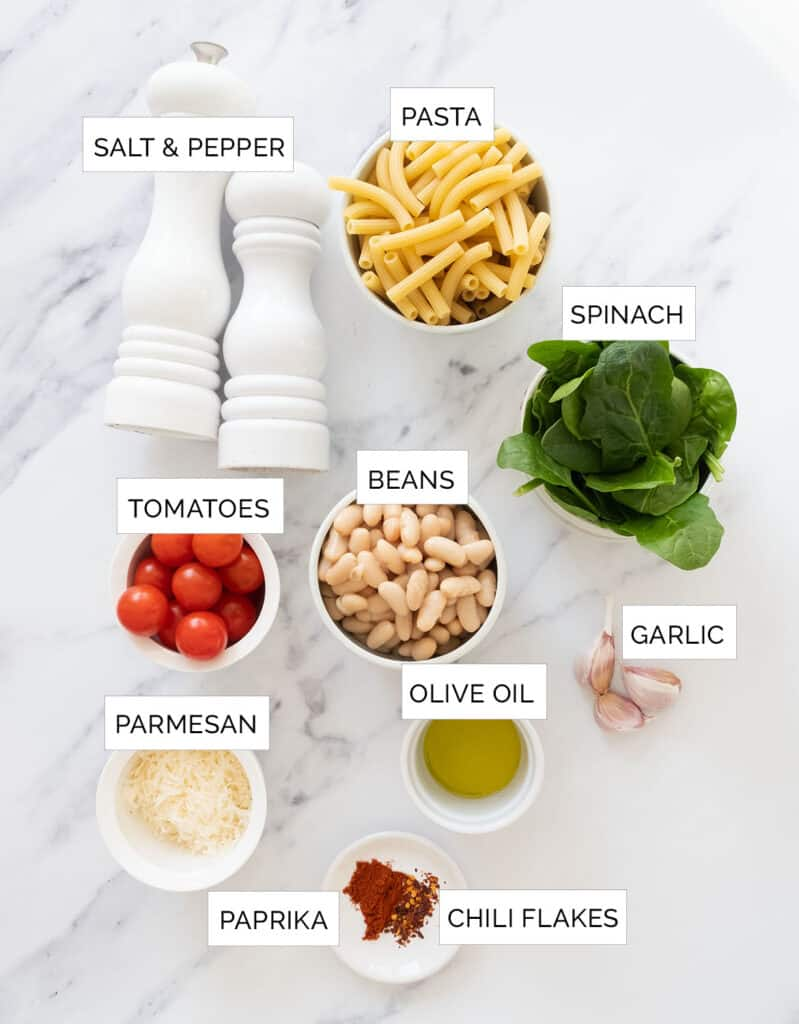 The ingredients for this white bean pasta are arranged over a white background.