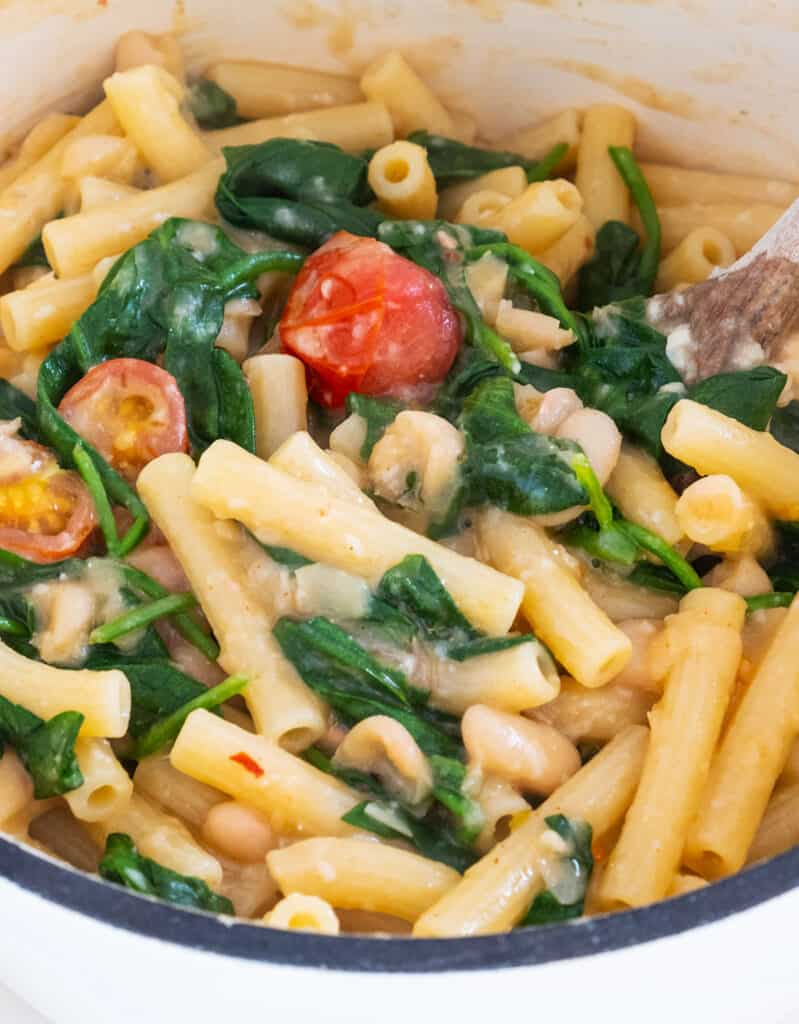 One pot full of white bean pasta with spinach and cherry tomatoes.