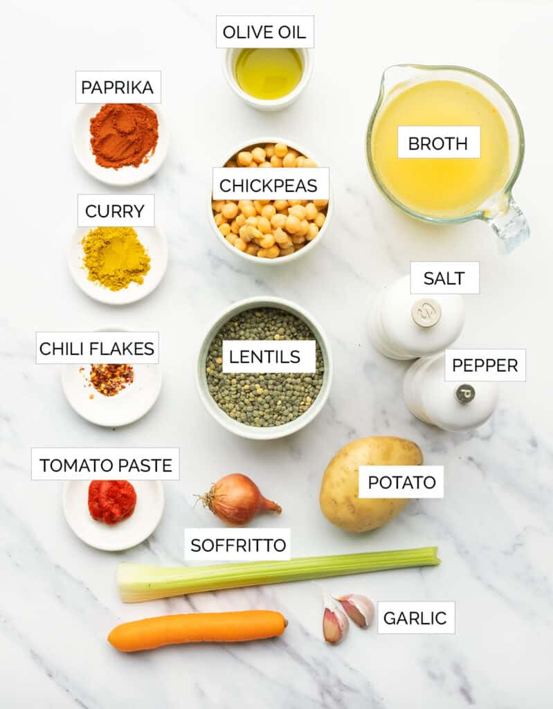 Top view of the ingredients to cook this smoky chickpea and lentil soup are arranged over a white background.