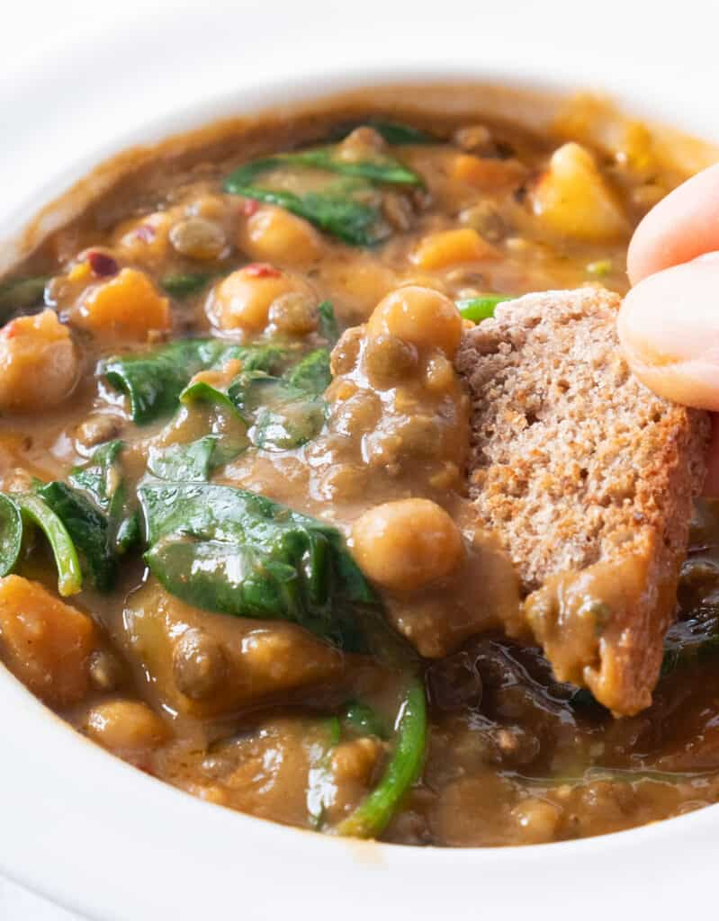 Close-up of a piece of bread dipping into the smoky chickpea and lentil soup with spinach.