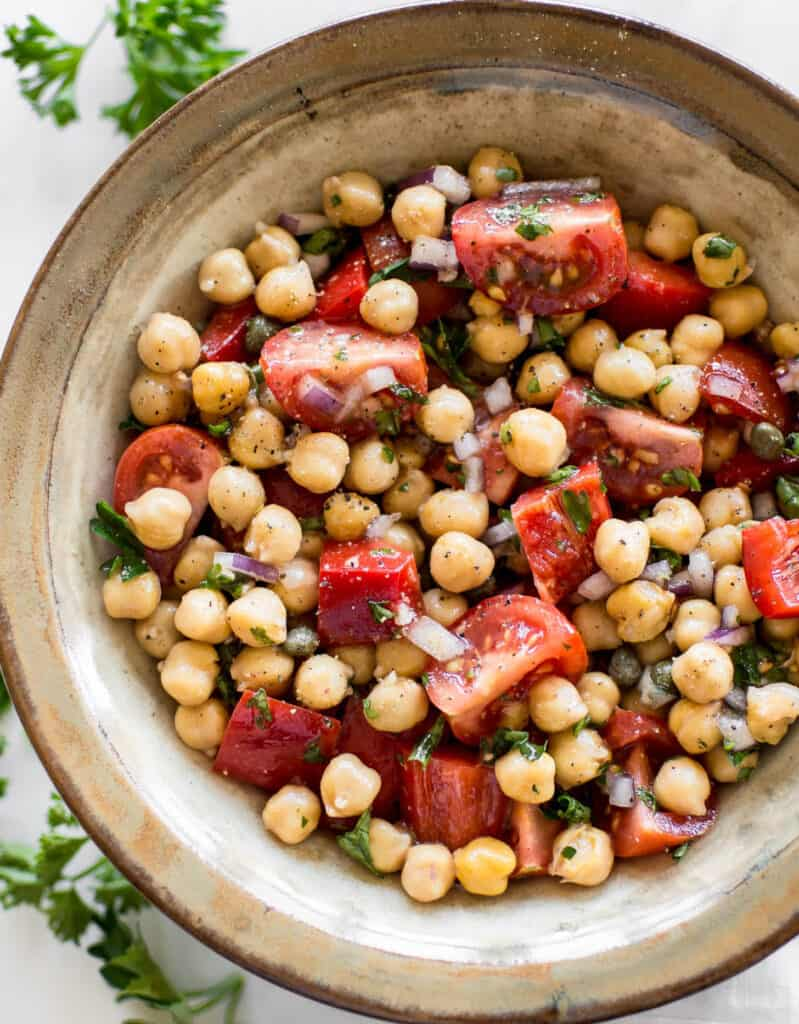 Top view of a large bowl full of chickpea salad with tomatoes over a white background - by Salt & Lavander