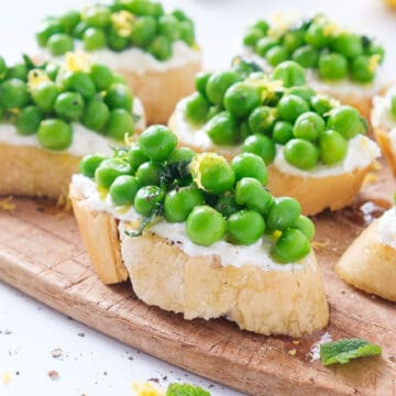 Close-up of a crostini with ricotta and peas on a small wooden board.