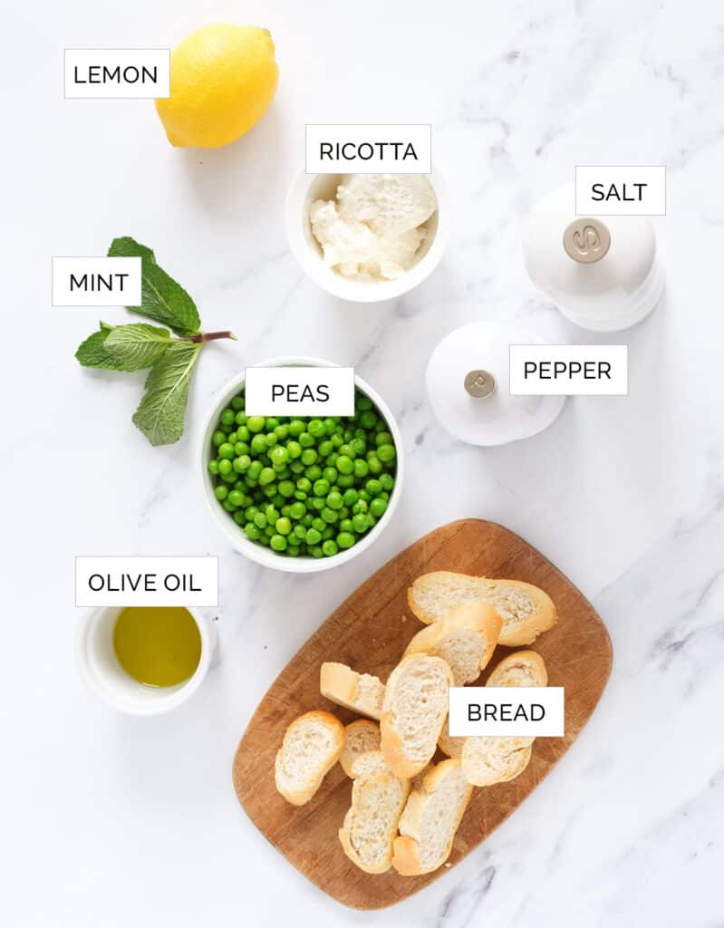 Top view of the ingredients to make crostini with ricotta and peas over a white marbled table.
