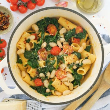 Top view of one pot pasta recipe with cherry tomatoes, white beans and spinach.