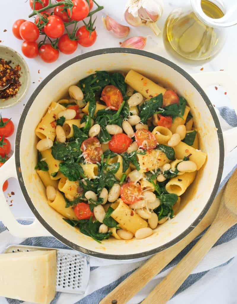 Top view of one pot pasta with white beans, cherry tomatoes and spinach.