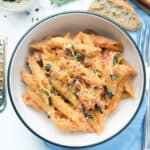 Top view of a bowl full of one-pot penne pasta with tomato sauce, basil and ricotta.