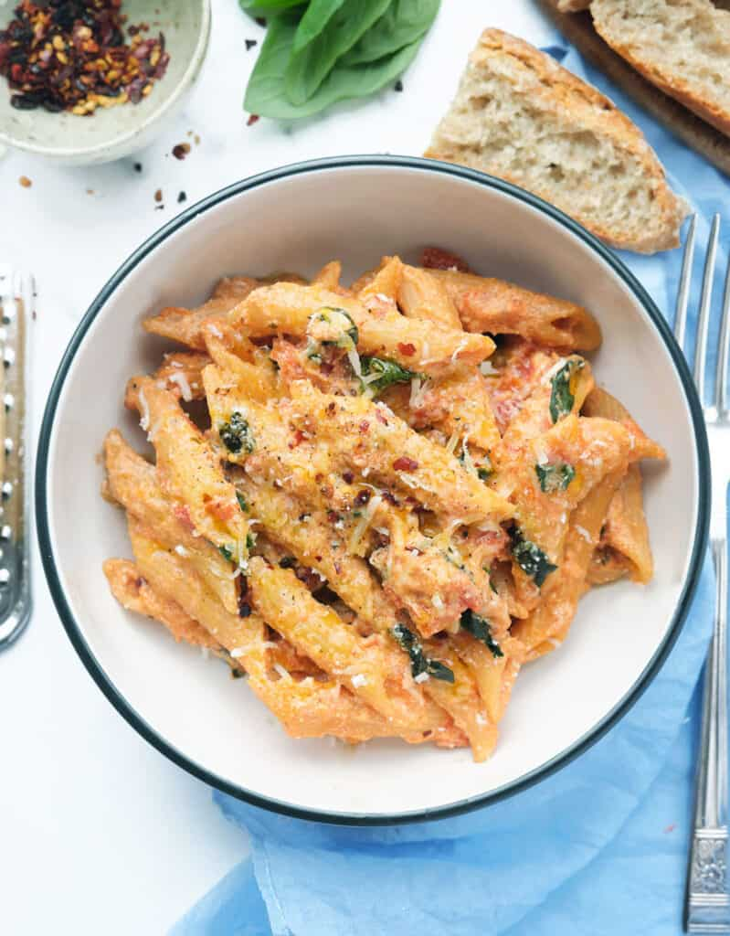 Close-up of a fork lifting some penne pasta with tomato sauce, basil leaves in the background.