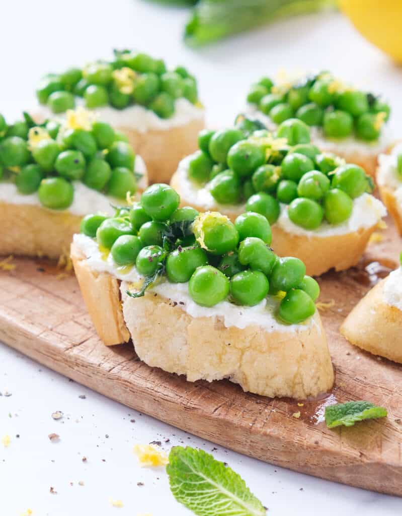 Close-up of some crostini topped with peas over a wooden board.