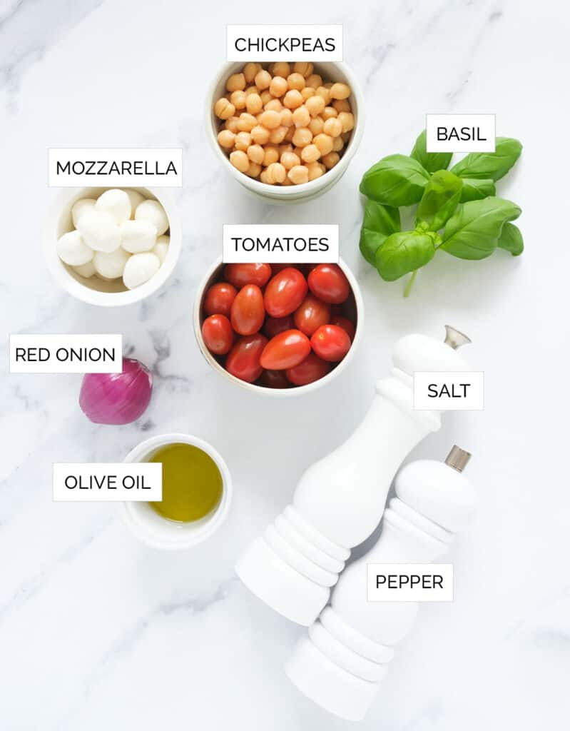Top view of the ingredients to make this Italian chickpea salad are arranged over a white background.