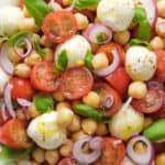 Close-up of a portion of Italian chickpea salad with cherry tomatoes, mozzarella and basil.