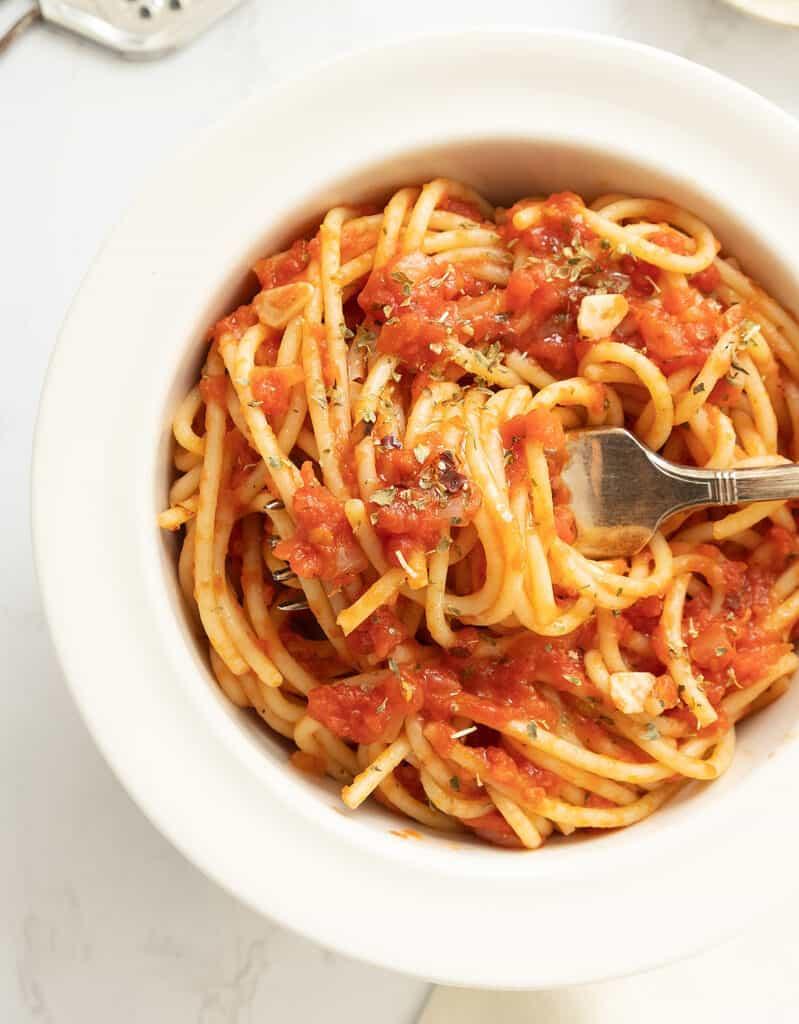 Top view of a white bowl full of spaghetti alla marinare over a white background.