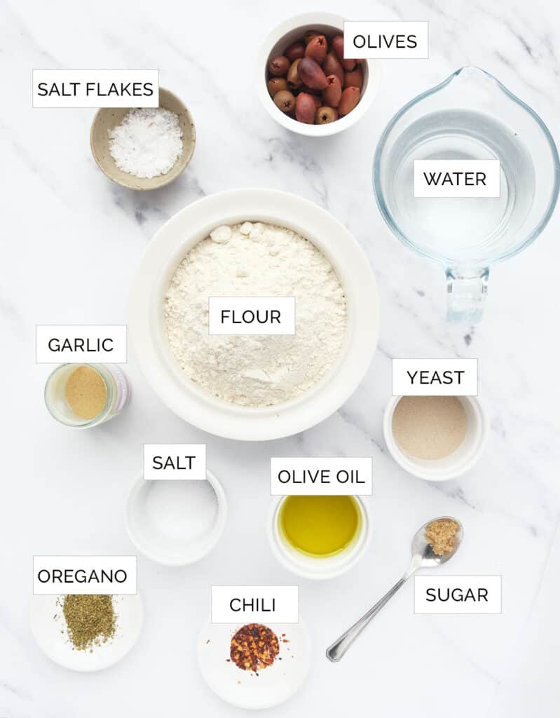 Top view of the ingredients to make focaccia with olives.