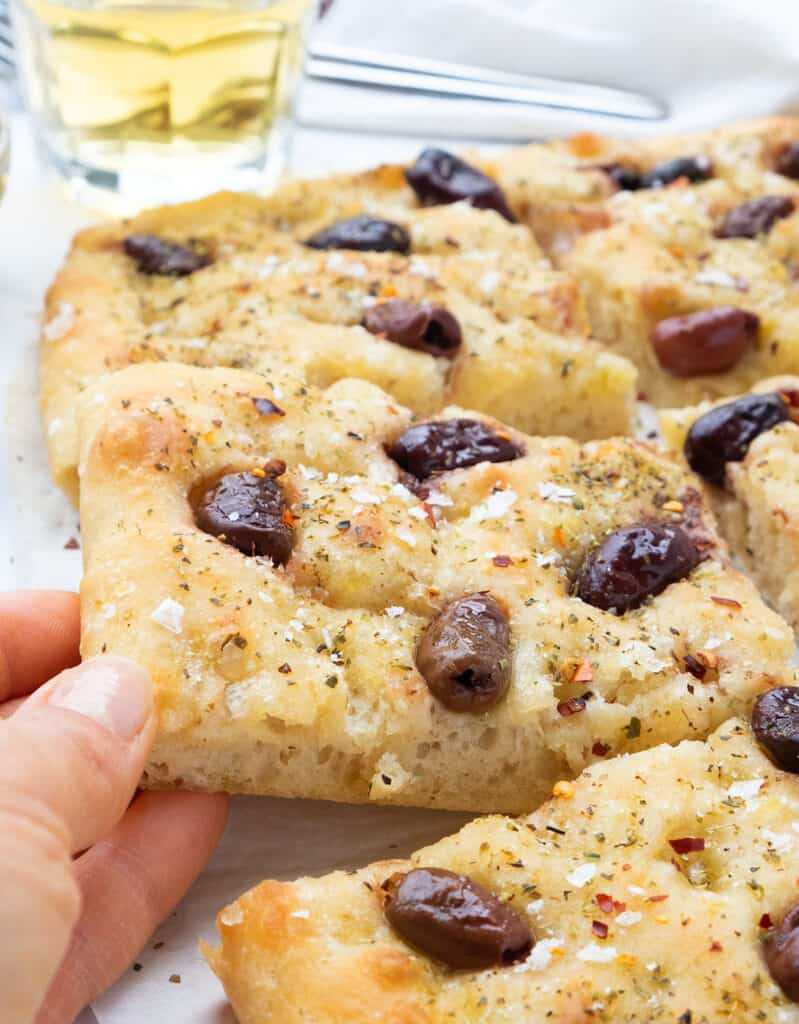 A hand grabbing a slice of olive focaccia, a glass of wine in the background.