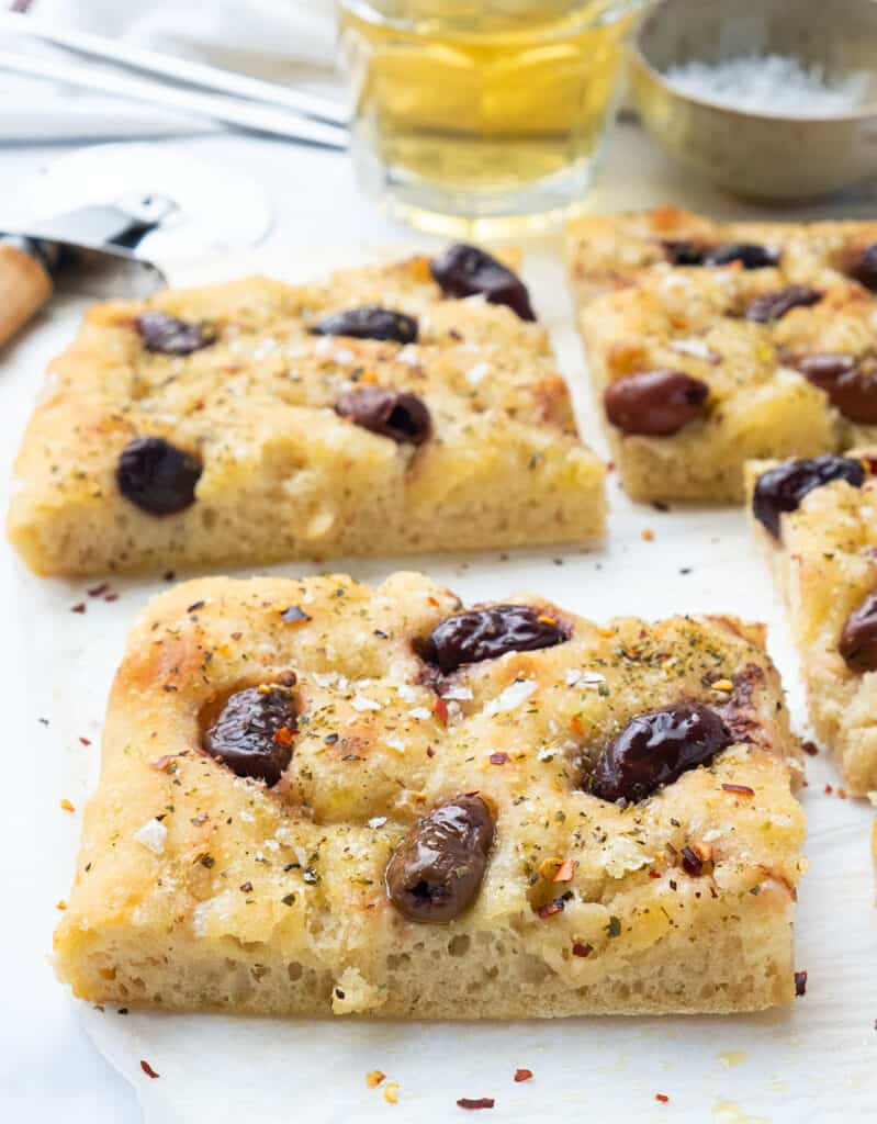 Focaccia with olives cut into slices over a white background.