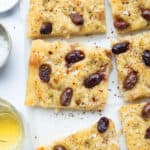 Top view of easy focaccia with olives cut into slices over a white background.