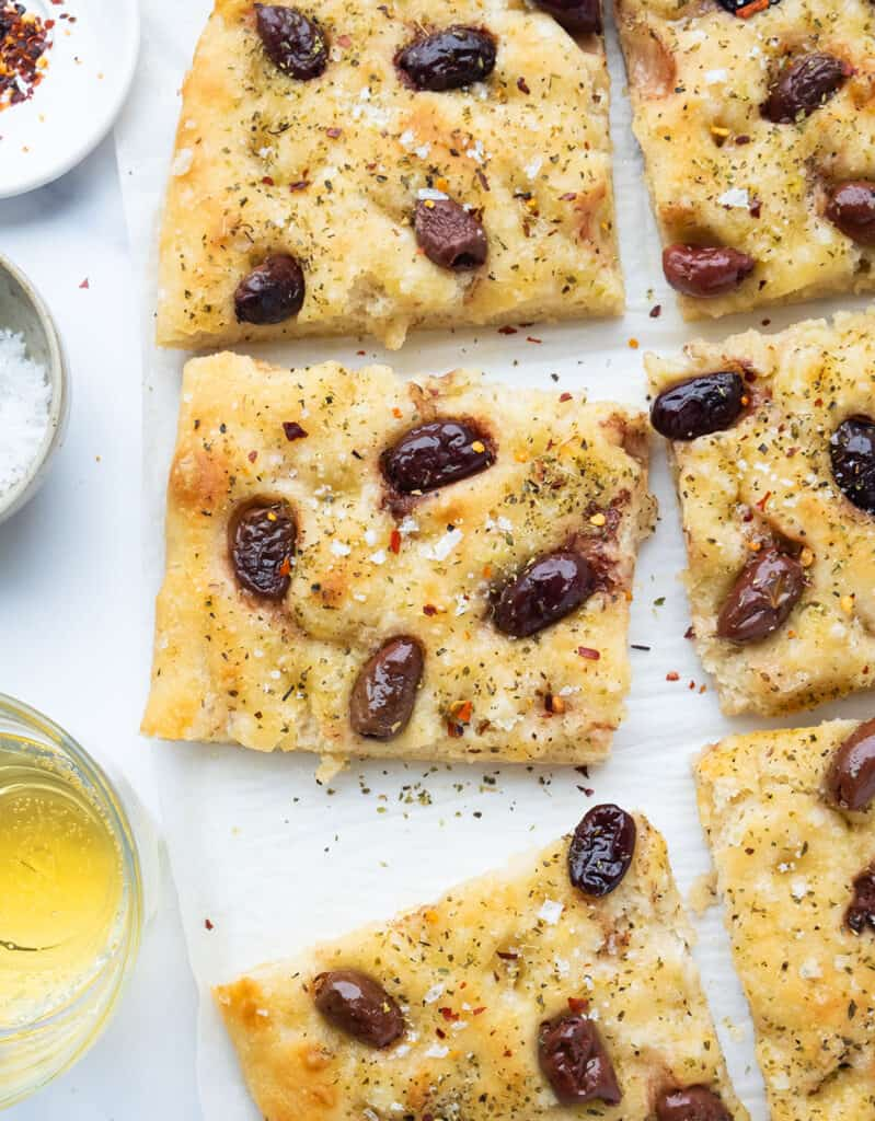 Top view of a large focaccia with olives cut into six slices over a white background.