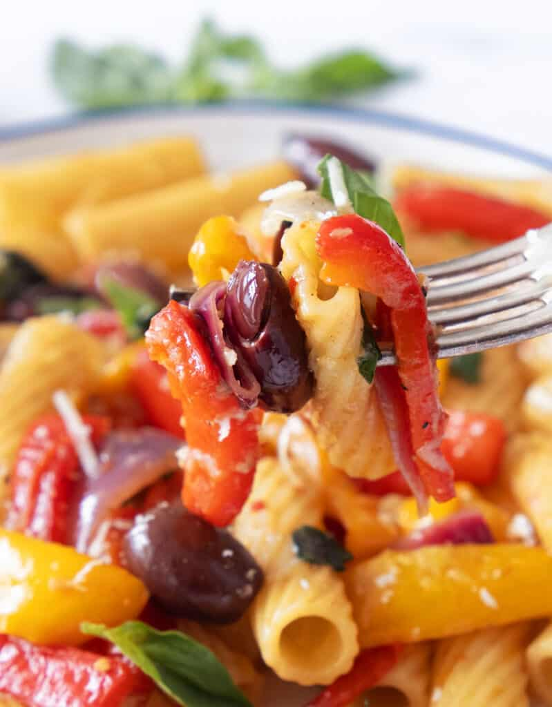 Close-up of a fork lifting some pasta with peppers and olives.